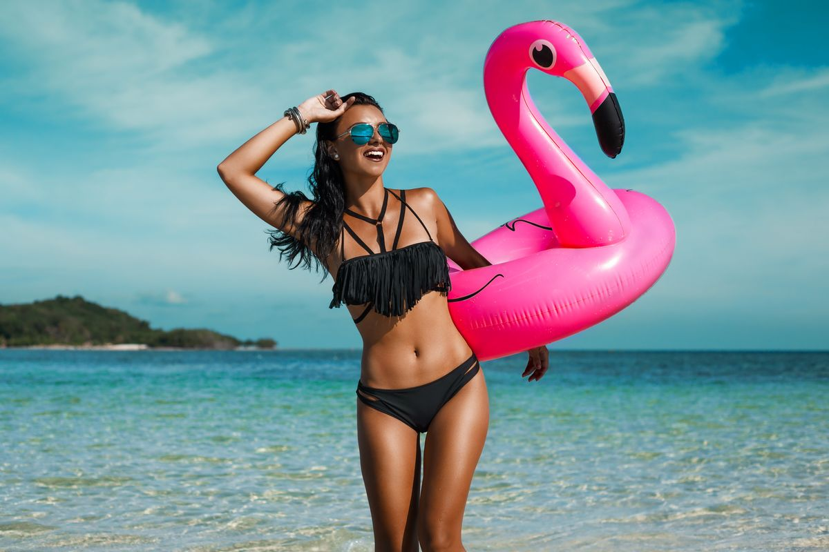 EstMed Pic - A beautiful sexy amazing young woman on the beach sits on an inflatable pink flamingo and laughs, has a great time, tanned perfect body, long hair, black bikini, fashion accessories, low key photo